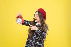 Fille avec le r?veil Installez le r?veil Horloge rouge de prise de petite fille d'enfant Il est temps Toujours ? l'heure Il n'est image stock