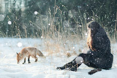 Fille avec le renard dans la forêt d'hiver Photographie stock