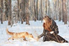 Fille avec le renard dans la forêt d'hiver Photographie stock libre de droits
