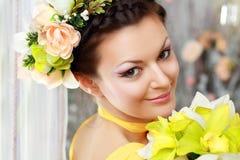 Fille avec le renivellement élégant et les fleurs Image stock