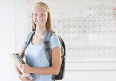 Fille avec le sac à dos et les livres se tenant dans la classe de chimie Photographie stock