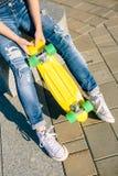 Fille avec le shortboard de planche à roulettes de penny Photographie stock libre de droits
