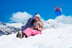 Fille avec le surf des neiges sur la station de sports d'hiver Photos libres de droits