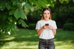 Fille avec le téléphone en parc photographie stock libre de droits