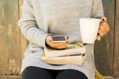 Fille avec le téléphone portable, la tasse de café et les livres Image stock