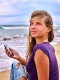 Fille avec le téléphone portable se reposant sur le sable près de la mer Photographie stock libre de droits