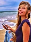 Fille avec le téléphone portable se reposant sur le sable près de la mer Photo libre de droits