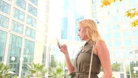 Fille avec le téléphone promenades un jour ensoleillé chaud dans une ville moderne fond des gratte-ciel 4K Mouvement lent clips vidéos