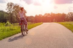 Fille avec le v?lo au coucher du soleil d'?t? sur la route en parc de ville Roue de plan rapproch? de cycle sur le fond brouill?  photographie stock