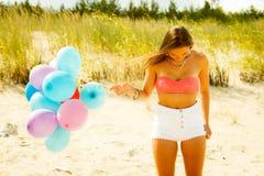 Fille avec les ballons colorés sur la plage Image libre de droits