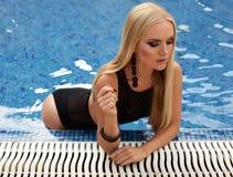 Fille avec les cheveux blonds dans le costume de natation, détendant près de nager le PO Image stock