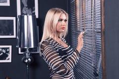 Fille avec les cheveux blonds regardant la fenêtre Photos libres de droits