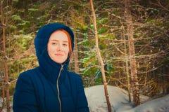 Fille avec les cheveux rouges dans un capot dans la forêt d'hiver image libre de droits