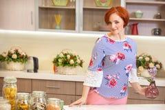Fille avec les cheveux rouges tenant des fleurs dans la cuisine Photos libres de droits