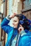 Fille avec les dreadlocks bleus écoutant la musique sur des écouteurs image libre de droits