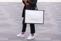 Fille avec les espadrilles blanches se tenant tenantes un sac à provisions de Gucci sur une rue photographie stock libre de droits