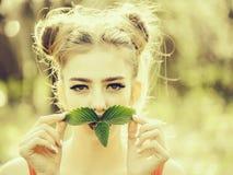 Fille avec les feuilles vertes photographie stock