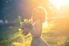 Fille avec les fleurs lilas Photos stock