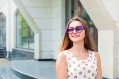 Fille avec les lunettes de soleil pourpres en forme de coeur recherchant pour dégrossir pour copier rêver de l'espace image libre de droits