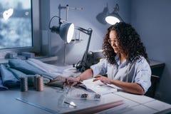 Fille avec les notes sérieuses de lecture de regard du carnet dans la soirée sur le lieu de travail Photos libres de droits