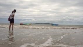 Fille avec les pieds nus se tenant sur une plage avec l'écrasement de vague dedans banque de vidéos