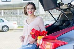 Fille avec les tulipes rouges se reposant dans le tronc de voiture Photo stock