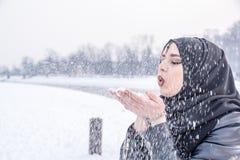 Fille avec les yeux bleus étonnants jouant avec la neige Photos libres de droits