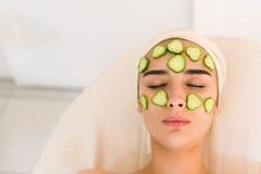 Fille avec les yeux fermés avec un masque des concombres Photographie stock libre de droits