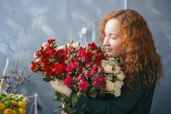 Fille avec les yeux fermants et enjoing de visage rose l'odeur des roses photographie stock