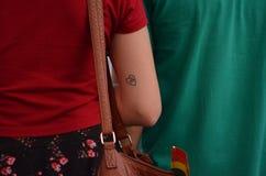 Fille avec peu de tatouage de coeur sur son bras photographie stock libre de droits