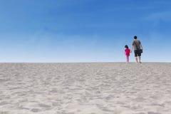 Fille avec sa promenade de père sur le désert Photographie stock libre de droits