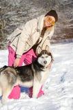 Fille avec son chien de traîneau mignon de chien sur une promenade photo stock