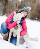 Fille avec son chien mignon dans la forêt d'hiver Photos stock