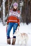 Fille avec son chien mignon dans la forêt d'hiver Image stock