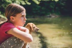 Fille avec son chien par le lac Image libre de droits