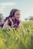Fille avec son chiot dans l'herbe Photo stock
