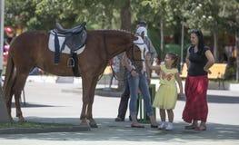 Fille avec tous nos remerciements de parents de l'équitation Photographie stock libre de droits