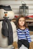Fille avec un bonhomme de neige de jouet Photos stock