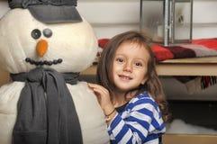 Fille avec un bonhomme de neige de jouet Photo stock