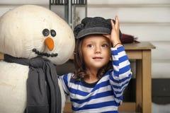 Fille avec un bonhomme de neige de jouet Photographie stock libre de droits
