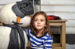 Fille avec un bonhomme de neige de jouet Photographie stock