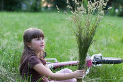 Fille avec un bouquet dans l'herbe Photo stock