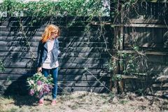 Fille avec un bouquet lilas de lilas dans le jardin fille déchirant le lilas dans le jardin Images stock