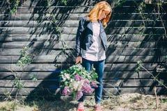 Fille avec un bouquet lilas de lilas dans le jardin fille déchirant le lilas dans le jardin Photographie stock libre de droits