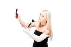 Fille avec un bras cassé essayant de mettre le maquillage Photographie stock libre de droits