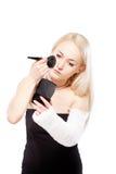 Fille avec un bras cassé essayant de mettre le maquillage Images libres de droits