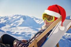 Fille avec un chapeau de Santa dans une chaise longue, fond neigeux de montagne Photographie stock libre de droits
