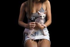 Fille avec un chat chauve sur ses mains sur un fond noir photographie stock