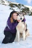 Fille avec un chien en hiver Photographie stock libre de droits