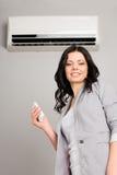 Fille avec un climatiseur à télécommande Image stock